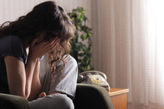 Woman crying. Depressed young woman sitting in chair at home Stock Image