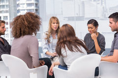 Woman crying during group therapy session. Woman crying during therapy session with other people and therapist Royalty Free Stock Images