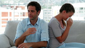 Woman crying while her boyfriend tries to explain himself. At home in the living room stock footage