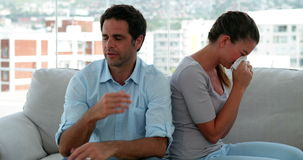 Woman crying while her boyfriend tries to explain himself. At home in the living room stock video footage