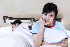 Woman crying while her husband sleeping Stock Images