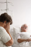 Woman crying next to her sick husband royalty free stock photography