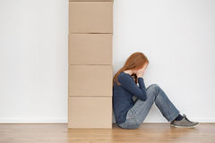 Woman Crying Next to Moving Boxes. A woman sitting against a stack of moving boxes and crying Royalty Free Stock Photo