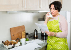 Woman crying over banking papers about delay of payment Stock Images