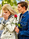 Woman crying after Quarreling With Man. Betrayal and forgiveness couple. Girl is crying with handkerchief on outdoor. Man holding red rose royalty free stock image