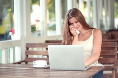 Woman crying she is so sad in front of a laptop stock photography