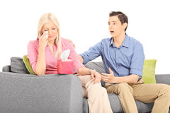 Woman crying seated on sofa with her boyfriend Royalty Free Stock Photography