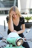 Sad woman on a scooter royalty free stock photos