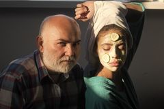 Woman with cucumber mask on face and towel on head. Girl and old men with beard and bold forehead. Youth, beauty, freshness, rejuvenate, decay, aging, age Stock Photography
