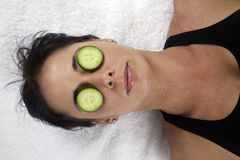 Woman with cucumber slices on her eyes. Woman lying on white towel, with cucumber slices on her eyes Stock Photos