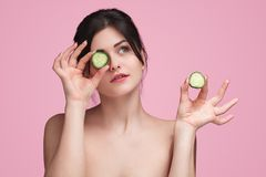 Woman with cucumber slices looking up. Pretty young brunette holding slices of fresh cucumber looking up while standing on pink background royalty free stock image