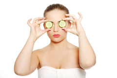 Woman with cucumbers on eyes Stock Images