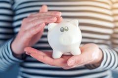 Woman cuddles piggy coin bank Royalty Free Stock Photos