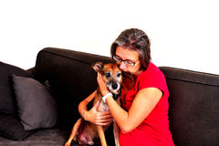 Woman cuddling with dog on a grey sofa Stock Photography