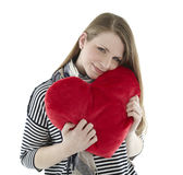 Woman cuddling with heart pillow Stock Photos