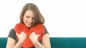 Woman cuddling with a heart pillow Royalty Free Stock Images