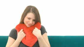 Woman cuddling with a heart pillow Stock Images
