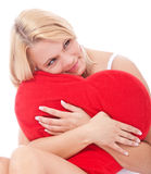 Woman cuddling heart shaped pillow Royalty Free Stock Photography