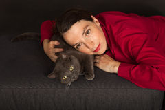 The woman is cuddling with her cat Stock Photography