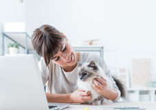 Woman cuddling her cat. Young woman sitting at desk and cuddling her lovely cat, togetherness and pets concept stock photo