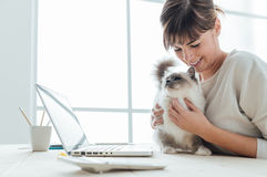 Woman cuddling her cat. Young woman sitting at desk and cuddling her lovely cat, togetherness and pets concept royalty free stock images