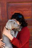 Woman cuddling pet dog. With face obscured, wooden background Royalty Free Stock Photo