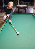 Woman with a cue behind a billiard table Royalty Free Stock Photography