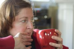 Woman with cup. Portrait of middle aged woman with red cup of tea or coffee Royalty Free Stock Images