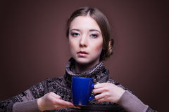Woman in with cup of aromatic coffee looking at the camera Stock Photography