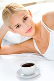 Woman with cup on bed Royalty Free Stock Photos
