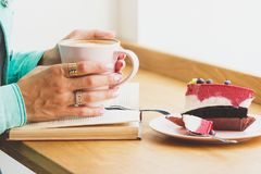 Woman with a cup of cappuccino and a piece of dessert on the plate Royalty Free Stock Photos