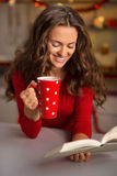 Woman with cup of chocolate and book in Christmas kitchen Stock Photos
