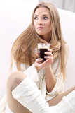 Morning with coffee. Long-haired blonde with a cup of coffee sitting on a sofa Royalty Free Stock Images