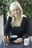 Woman with cup of coffee. Happy young blond woman sat in cafe with cup of coffee stock images