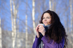 Woman with cup of coffee. Smiling woman with cup of coffee in the winter park Royalty Free Stock Photo