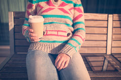 Woman with cup of coffee and digital tablet on bench Stock Images