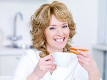 Woman with cup of coffee having breakfast. Laughing young beautiful woman with cup of coffee having breakfast - indoors Stock Photo