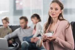 Young woman holding a cup of coffee and looking at camera while her family is sitting royalty free stock image