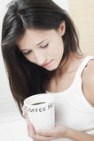 Woman with a cup of coffee lost in memories Stock Photo