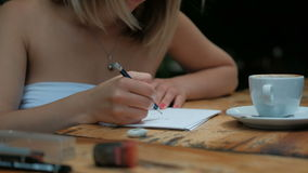 Woman with a cup of coffee makes a pencil sketch on paper. Blonde in cafe at a table doing sketches on the sheet and using the eraser erases the line. She stock footage