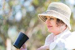 Woman  with cup of coffee  in nature. Woman in hat  sitting  in nature and holding a  cup of coffee Stock Photography