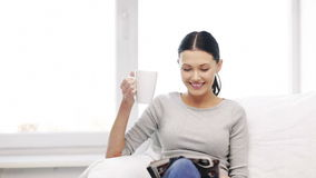 Woman with cup of coffee reading magazine at home stock video footage