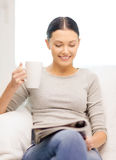Woman with cup of coffee reading magazine at home royalty free stock photos