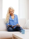 Woman with cup of coffee reading magazine at home Stock Photos