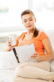 Woman with cup of coffee reading magazine at home. Smiling woman with cup of coffee reading magazine at home Stock Images