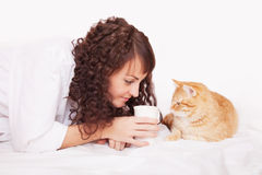 Woman with a cup of coffee and red cat. Woman with a cup of coffee and a cat in bed Royalty Free Stock Photography