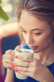Woman from a cup of coffee with steam Stock Photography