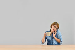 Woman with cup of coffee talking on phone Royalty Free Stock Image