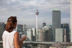Woman with a cup of coffee on the top floor of a skyscraper admires the view of Kuala Lumpur. Stock Photos
