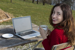 Woman with a cup of coffee working on computer outdoors Stock Images